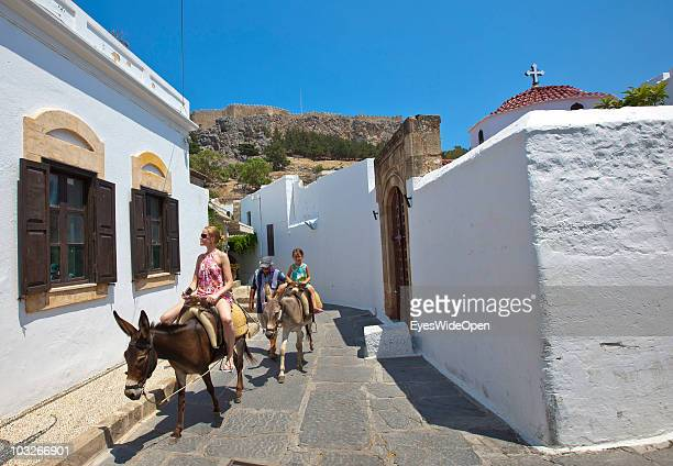 Tourists and children riding on donkeys back from the Acropolis of Lindos on July 04 2010 in Lindos Greece The old town of Lindos is famous for its...