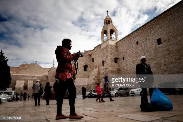 Tourists and Christian pilgrims take pictures outside of the Church of the Nativity, revered as the site of Jesus Christ's birth, in the occupied...
