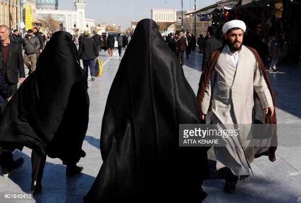 Tourists and clerics walk near the Massoumeh shrine in the holy city of Qom 130 kilometres south of Tehran on December 14 2017 / AFP PHOTO / ATTA...