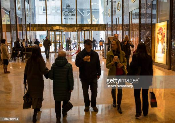 Tourists and curiosity seekers visit the Trump Tower lobby March 20 2017 along Fifth Avenue in New York City The 58story luxury condominium building...