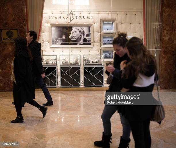 Tourists and curiosity seekers visit Trump Tower March 20 2017 along Fifth Avenue in New York City The 58story luxury condominium building has three...