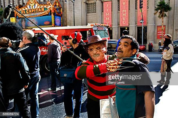 Tourists and film character lookalikes with Freddy Kreuger strangling a visitor outside Mann's Chinese Theatre on Hollywood boulevard Wannabe actors...