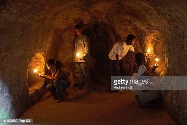 tourists and guide with candles looking at burial chambers tombs - horn of africa ストックフォトと画像