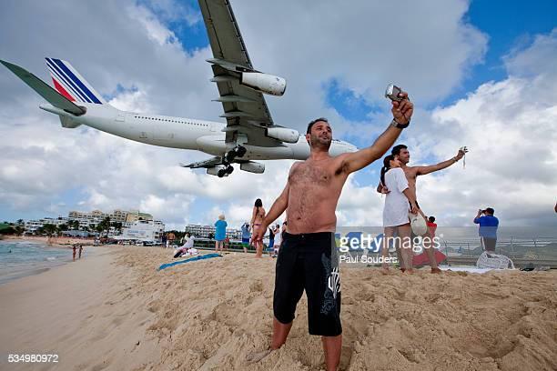 Tourists and landing jet at St. Maarten, Netherlands Antilles