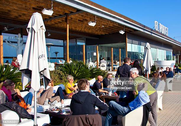 Tourists and local people relax in the sun at the Zensa Bar at Denia Harbour with luxury yachts, fishing boats, tourist sightseeing boats, bars and...