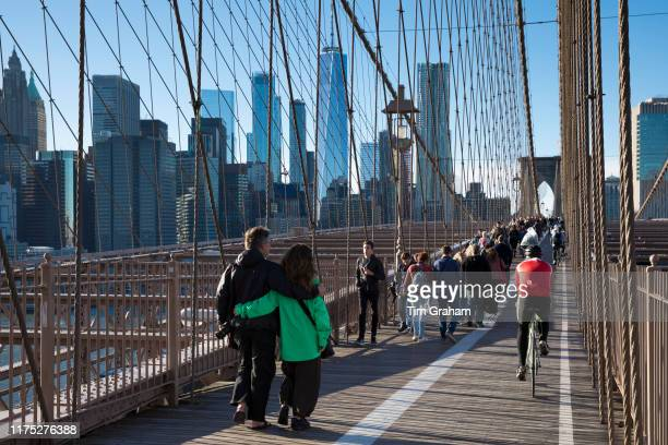 Tourists and local people stroll and cycle across Brooklyn Bridge towards Manhattan New York City
