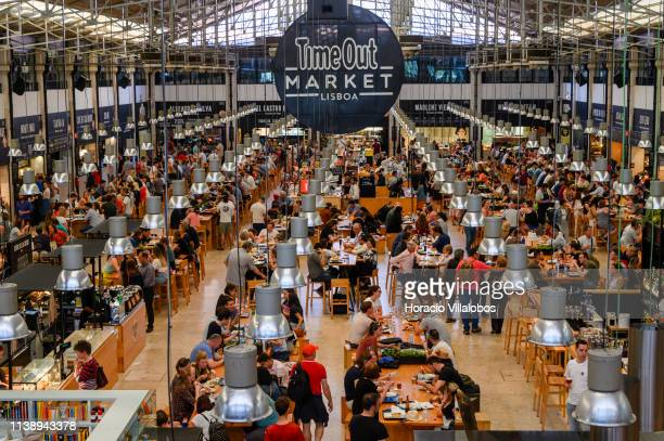 Tourists and locals crowd Time Out Mercado da Ribeira Lisbon main market hall transformed into a foodie hangout that brings together some of the...