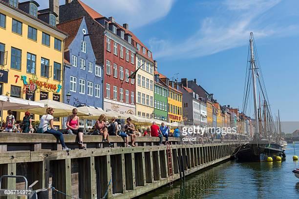 Tourists and Locals Enjoy the Sunlight at Nyhaven, Copenhagen, Denmark