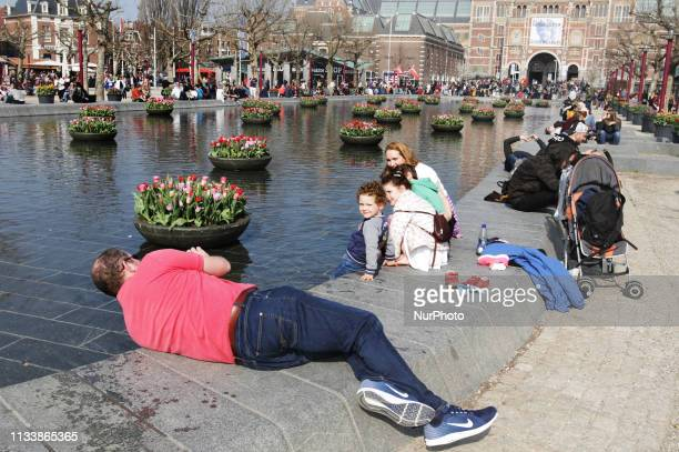 Tourists and locals enjoying next to the tulips in displayed by the fountain in front of the Rijksmuseum at Museumplein during the 5th edition of the...