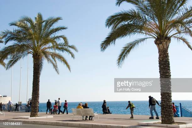 tourists and locals exercising and relaxing on the promenade des anglais nice france. - lyn holly coorg stock pictures, royalty-free photos & images