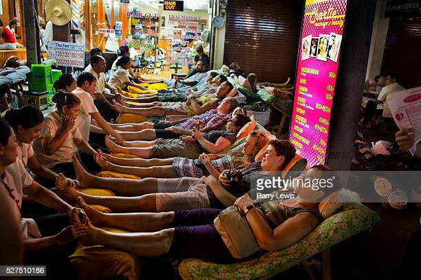 Tourists and locals lie down in rows for traditional Thai foot massage in Khao San Road, Bangkok, Thailand.