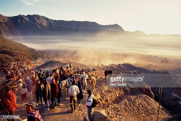 Tourists and locals ride or walk across the sands at Mount Bromo the spectacular volcanic peak situated high up in Indonesia'sTengger mountains an...
