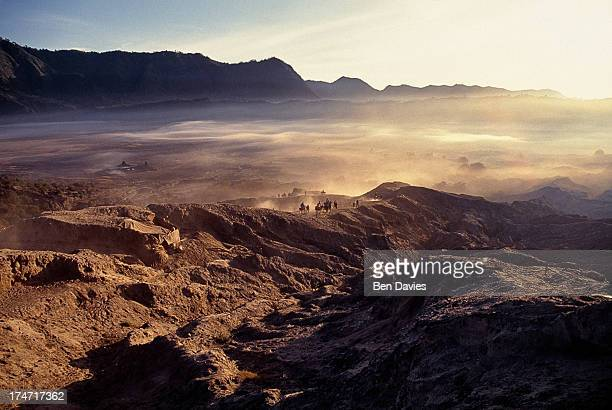 Tourists and locals ride or walk across the sands at Mount Bromo the spectacular volcanic peak that is situated high up in the Tengger mountains an...