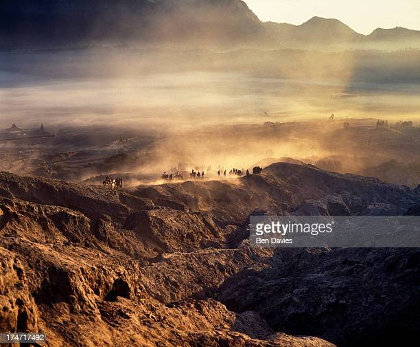 Tourists and locals ride or walk across the sands at Mount Bromo the spectacular volcanic peak that is situated high up in the Tengger mountains on...