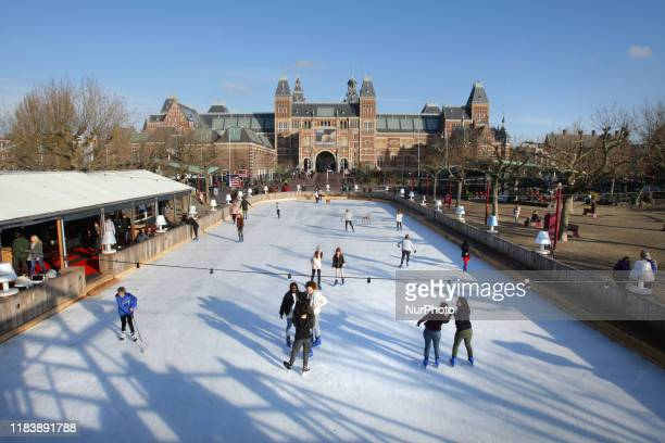 Tourists and locals skating on the ice rink in front of the Rijksmuseum in the Museum Square during sunny winter day on November 22 2019 in...