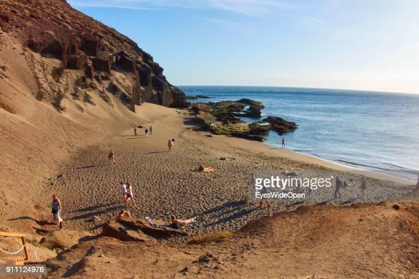 Tourists and locals tan at a sunbath at the sandy nudist nude bathing beach of Playa de la Tejita on January 10 2018 in El Medano Tenerife Spain