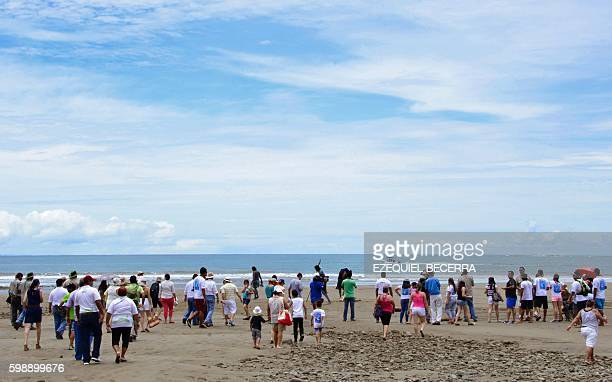 Tourists and locals walk to the shore of Bahia Ballena Beach in Puntarenas, about 230 km southwest of San Jose, on September 2, 2016 to see humpback...