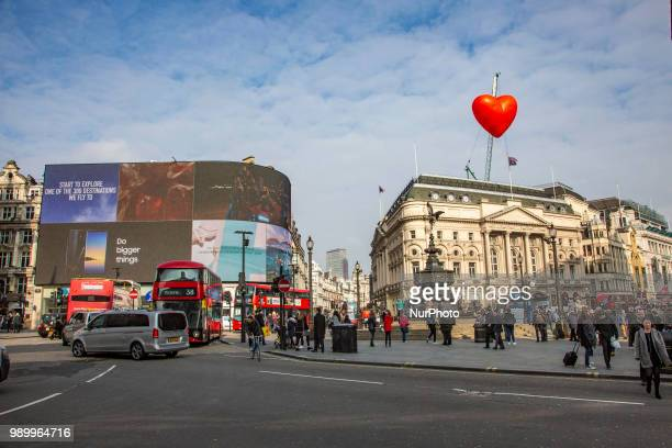 Tourists and locals walking in Piccadilly Circus or sitting on the steps of the Shaftesbury Memorial Fountain in Piccadilly Circus in City of...