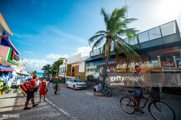 Tourists and man on bicycle in Playa Carmen city center, Mexico