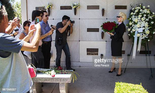 Tourists and Marilyn Monroe fans photograph Marilyn lookalike Kassandra Carroll as she brings a bouquet of red roses to the grave site on the 52nd...