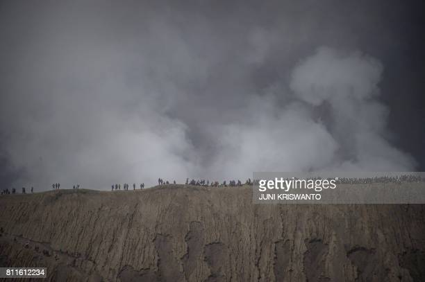 TOPSHOT Tourists and members of the Tengger tribe climb mount Bromo during the Yadnya Kasada Festival in Probolinggo on July 10 2017 Members of the...