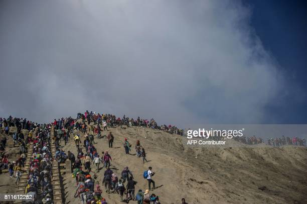 Tourists and members of the Tengger tribe climb mount Bromo during the Yadnya Kasada Festival in Probolinggo on July 10 2017 Members of the Tengger...