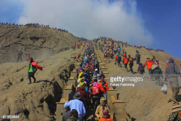 Tourists and members of the Tengger tribe climb mount Bromo during the Yadnya Kasada Festival on July 10 2017 in Probolinggo East Java Indonesia...