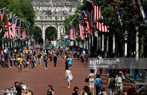 Tourists and pedestrians walk along the US and Union flaglined Mall leading to Buckingham Palace in central London on June 2 ahead of a visit to the...