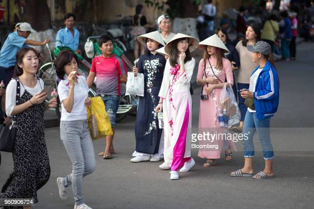 Tourists and pedestrians walk past women in traditional Vietnamese Ao Dai dress in the old town of Hoi An Qung Nam Province Vietnam on Friday April...