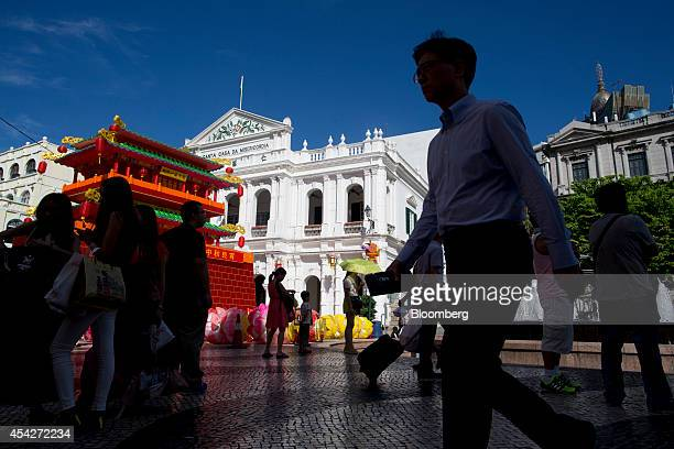 Tourists and pedestrians walk through Senado Square in Macau China on Tuesday Aug 26 2014 Macau is scheduled to release gross domestic product...