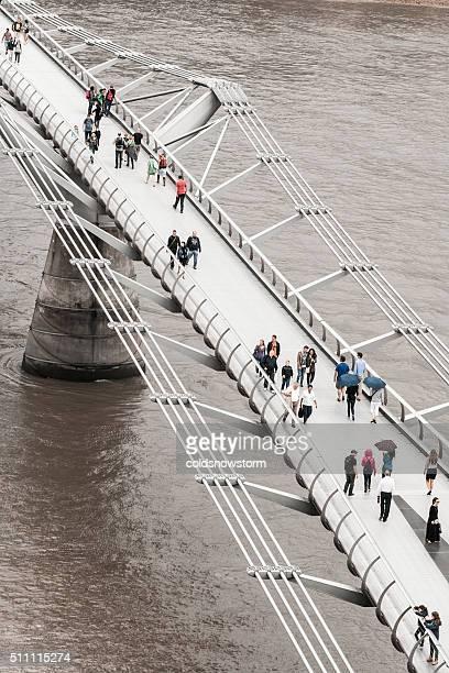 Tourists and Pedestrians walking across Millennium Bridge, London, UK