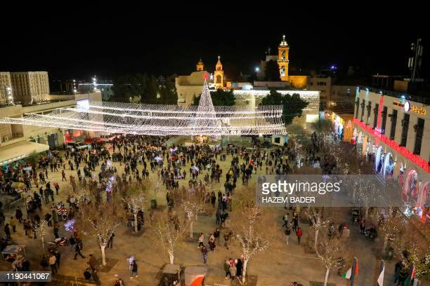 Tourists and pilgrims visit the Manger Square outside the Church of the Nativity in the biblical West Bank city of Bethlehem on December 24 2019...