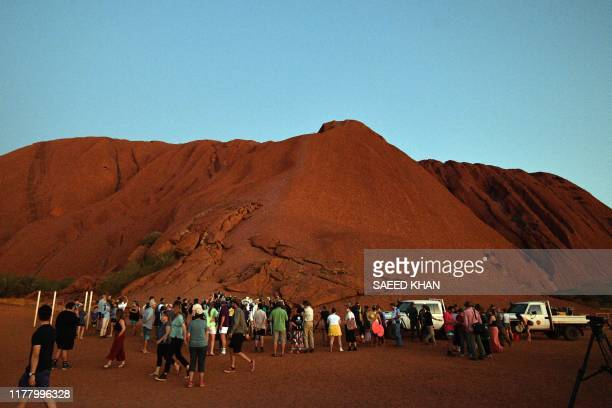 Tourists and residents are seen near Uluru, also known as Ayers Rock, following the day's close marking the start of a permanent ban on climbing the...