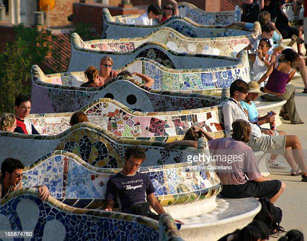CONTENT] Tourists and residents of Barcelona enjoy a sunny afternoon in the landmark Park Guell designed by Antonio Gaudi The people are reading...