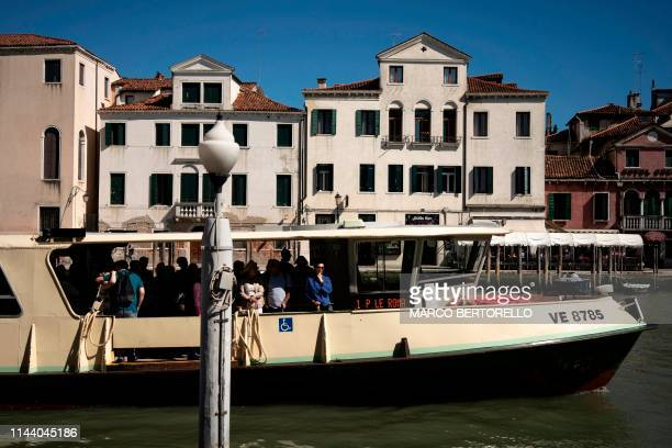 Tourists and residents stand on a vaporetto boat on the Grand Canal in Venice, on May 16, 2019.