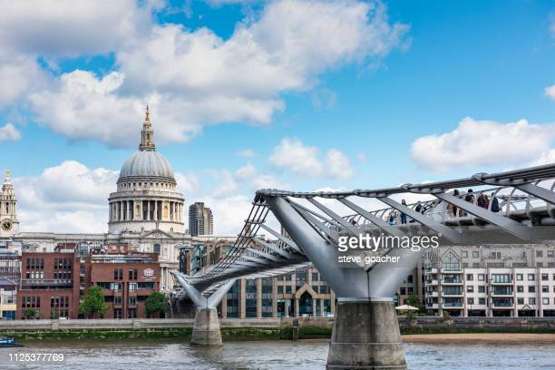 tourists and residents traversing the river thames on the london millennium footbridge, england. - greater london stock pictures, royalty-free photos & images