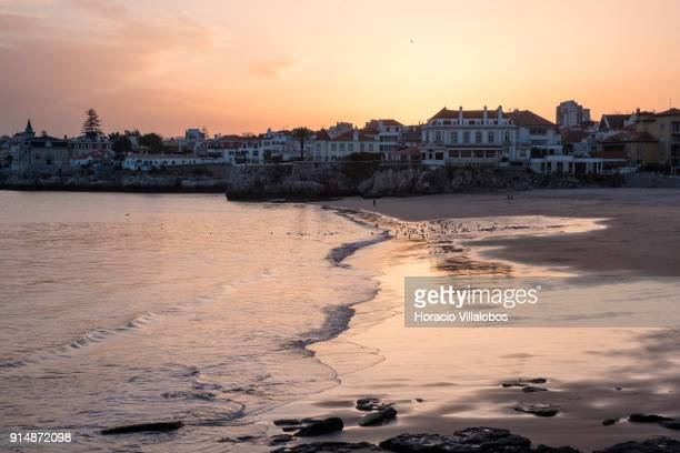 Tourists and seagulls at sunset enjoy mild winter weather at Praia da Duquesa on January 30 2018 in Cascais Portugal Mild and sunny winter weather is...