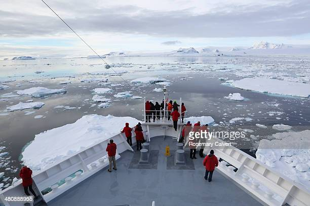 Tourists and ship in frozen Antarctic Sound.