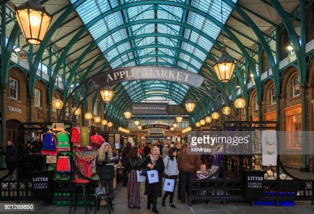 Tourists and shoppers walking through Covent Garden Market in London