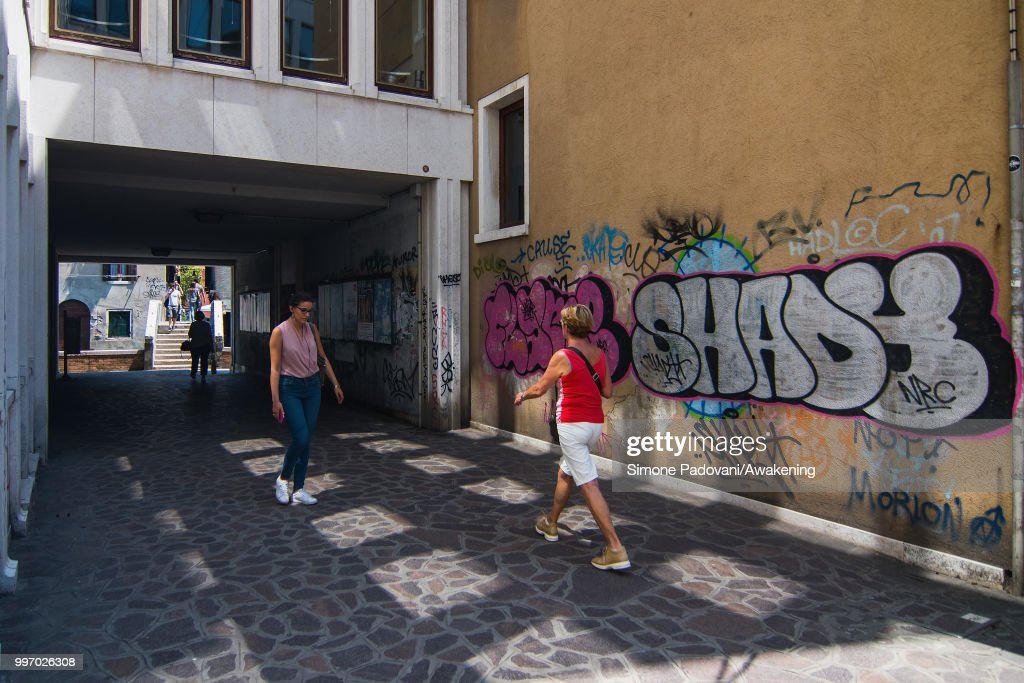 Tourists and students walk in Calle Contarina, along the Ca' Foscari University, through Dorsoduro district, on July 12, 2018 in Venice, Italy. The plague of graffiti and tags on the walls of the palaces of Venice continues with new writing across the doors, windows and the plaster of shops, banks, historic buildings, ruining and attacking the priceless architectural heritage of the lagoon. Venice has been living with this problem for years, but it has not reached a resolution until today.