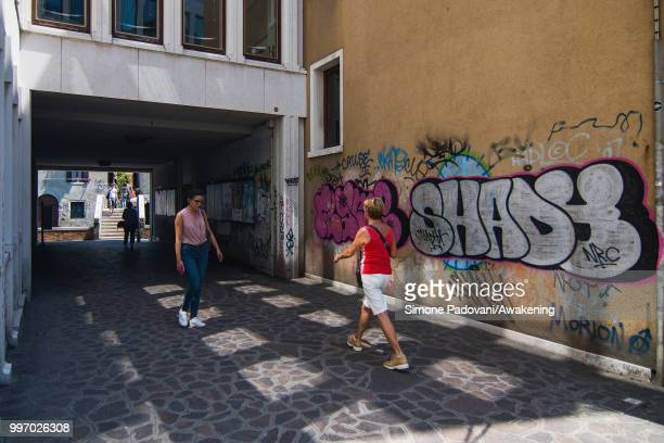 Tourists and students walk in Calle Contarina along the Ca' Foscari University through Dorsoduro district on July 12 2018 in Venice Italy The plague...