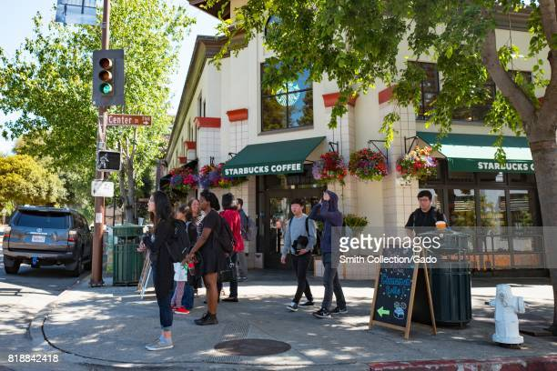 Tourists and students walk past a Starbucks Coffee cafe at the corner of Center Street and Oxford Street in a trendy section of downtown Berkeley...