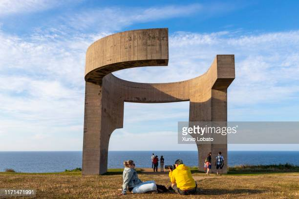 """Tourists and travelers take photos in front of the """"Praise of the Horizon"""" Sculpture by Eduardo Chillida in Cimadevilla Park ,as seen July 15, 2019..."""
