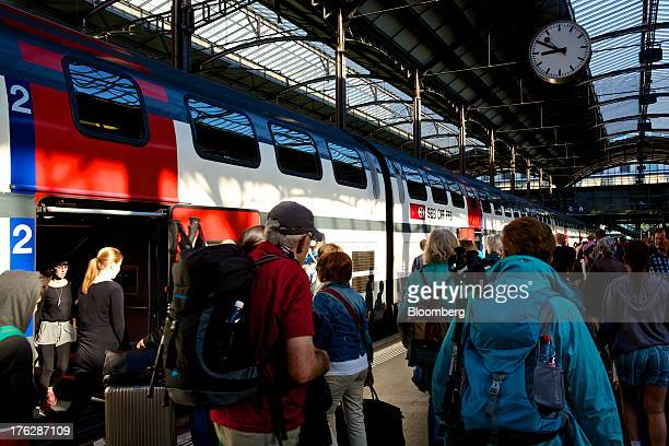 Tourists and travelers walk along a rail platform near a state operated SBB AG passenger train at Lucerne main train station in Lucerne Switzerland...