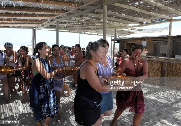 Tourists and Tunisians on vacation help prepare the buffet of traditional Tunisian cuisine at the Pirate restaurant on Pink Flamingo Island on August...