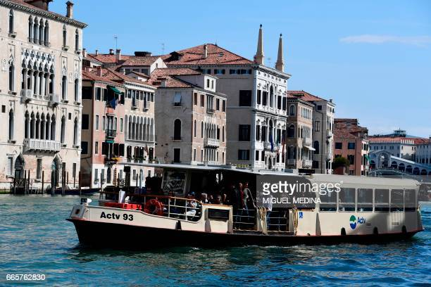 Tourists and Venetians stand on a vaporetto boat on the Grand Canal in Venice on April 7, 2017.