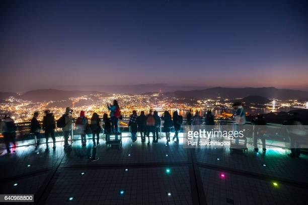 tourists and view of nagasaki city at mt.inasa observatory - nagasaki prefecture stock pictures, royalty-free photos & images