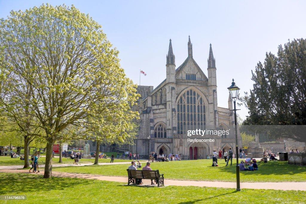 Los turistas y visitantes sentados alrededor de la famosa catedral de Winchester en el cálido Domingo de Pascua Sunshine a finales de abril : Foto de stock