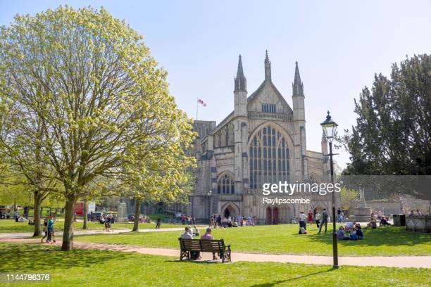 tourists and visitors sitting around the famous winchester cathedral in the warm easter sunday sunshine in late april - winchester hampshire stock photos and pictures