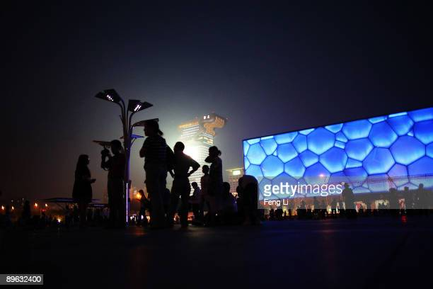 Tourists appreciate the night scene outside the National Aquatic Center known as Water Cube on August 6 2009 in Beijing China The Olympic Green has...